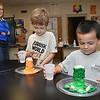 Pam Hamrick, left, watch  Bryson Thompson and Brayden Havens, make volcanoes then erupt them by pouring vinegar into baking soda during the STEM Camp held at Summers Co. High School.<br /> (Rick Barbero/The Register-Herald)
