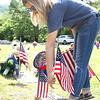 Westside FLP cadet captain Ashton Brown placing a flag on a Veteran's grave.