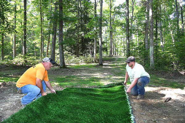 J.E. Daniel, maintenance foreman Lake Stephens, left, and Kevin Cantley, asst. maintenance foreman, position a piece of astroturf that was donated the tee box on the first hole of the new Disc Golf Course getting installed at Lake Stephens.<br /> (Rick Barbero/The Register-Herald)