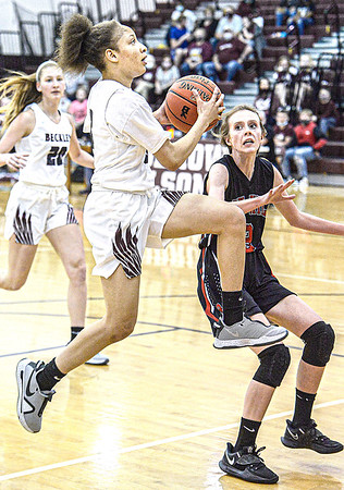 Woodrow Wilson's Keanti Thompson, left, drives for the score as Oak Hill's Eden Gilkey defends during Tuesday evening action in Beckley. F. Brian Ferguson