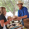 Emma Lightner buys a melon from Milton Brenneman at the Alderson Community Market Tuesday. Every Tuesday, children can try a bite of fresh fruit or vegetables and earn four Carrot Club Dollars ($4) to spend at the market for local produce. Jenny Harnish/The Register-Herald