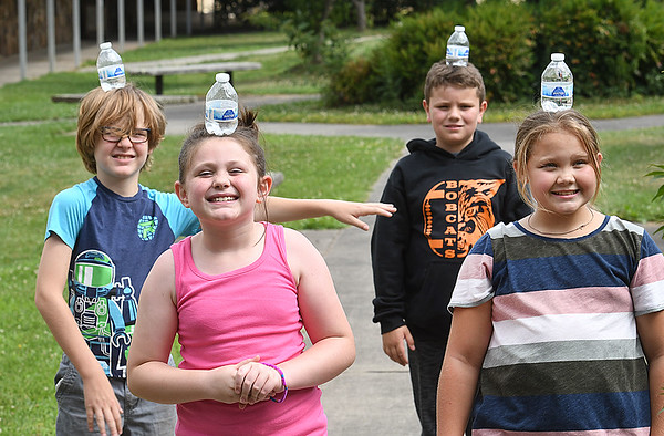 Gavin Martinez, left, Chloe Ball, Ethan Phillips and Chloe Grimmett, learned how other counties balance water on their heads during STEM Camp held at Summers Co. High School.<br /> (Rick Barbero/The Register-Herald)