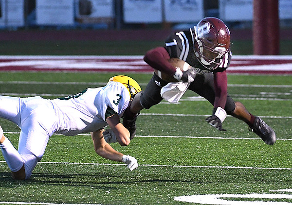 Tyiai Kimble, of Woodrow Wilson, right, gets tackled by, Bryson Ormsbee, of Greenbrier East, during game held at VanMeter Stadium in Beckley Friday night.<br /> (Rick Barbero/The Register-Herlad)