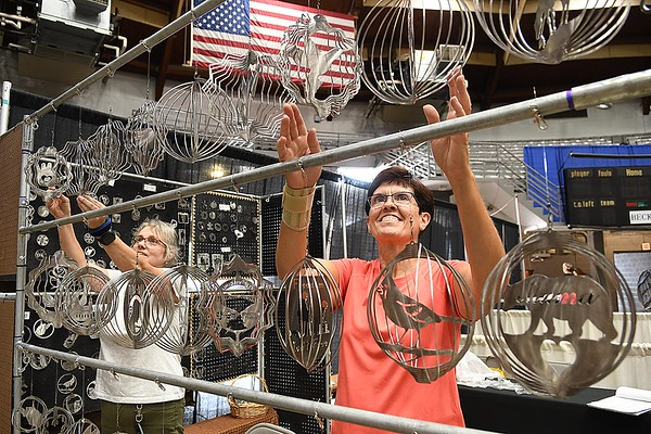 Tammi Hackworth, owner, Hackworth's Wood and Steel in Pax and Cathy Weaver, volunteer, set up wind spinners in their booth at the Beckley-Raleigh County Convention Center preparing for the opening of the Appacachian Makers Market that wil be held with fifty vendors on Friday 9 am to 7 p.m. and Saturday 9 am to 5 p.m. <br /> (Rick Barbero/The Register-Herald)