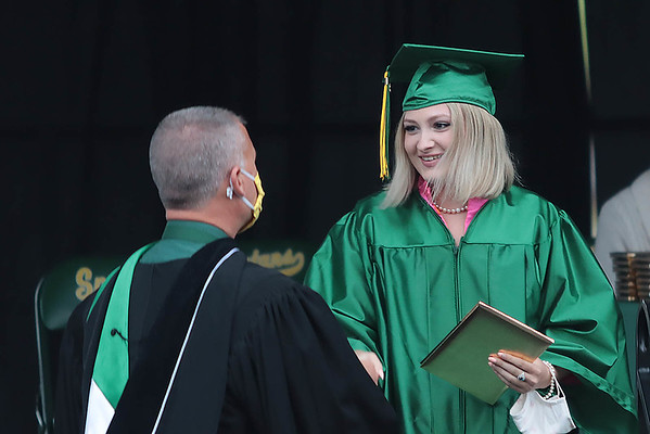 Courtney Foren shakes Principal Ben Routson after receiving her diploma from Greenbrier East High School at the 52nd Annual Commencement ceremony in Fairlea Friday.  Jenny Harnish for the Register-Herald