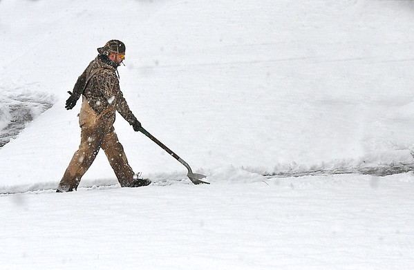 A guy shovels a sidewalk at Maxwell Woods Apartments in Beckley Thursday morning.<br /> (Rick Barbero/The Register-Herald)