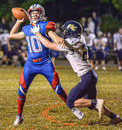 F. Brian Ferguson/Register-Herald Midland trail QB Joshua Dickerson gets off a pass as Nicholas County's Wes Hill brings pressure during Friday action in Hico.