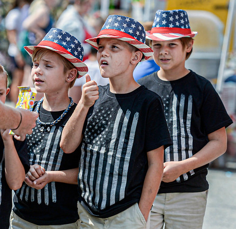 F. Brian Ferguson/Register-Herald  Brothers Easton Shay, 8, left, Landon Shay, 10, and Daniel Shay, 11, right, take in Saturday's Fayetteville's July 4th parade.
