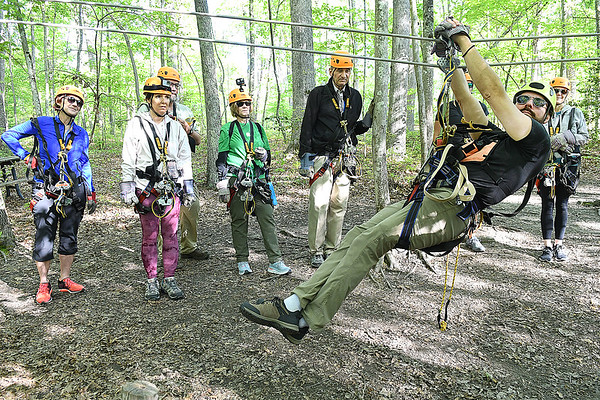 Matt Cook, guide, demonstrates on a zipline to member of the Freelance Council of the Society of American Travel Writers for the TreeTops Zipline Canopy Tours at Adventure On The Gorge Wednesday morning. Forty-one Travel Writers are exploring and writing about West Virginia this week.<br /> (Rick Barbero/The Register-Herald)
