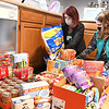 Angel Brandstetter, troop leader 51264, left and Gracie Clifton, girl scout troup 51264, stacks up $325. of nonperishable food items that were donated by the Girl Scouts for the Angels Program at One Voice on South Kanawha Street in Beckley. The troop has donated and worked with One Voice in the past and knew this was the right choice for them to donate. <br /> (Rick Barbero/The Register-Herald)