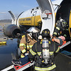Members of Beaver Volunteer Fire Department remove a passenger from a simulator airplane during a mock disaster plane wreck held at the Raleigh County Memorial Airport in Beaver Tuesday morning. This was a training excerise that's conducted every three years for airport employees to be FAA certifield.<br /> (Rick Barbero/The Register-Herald)