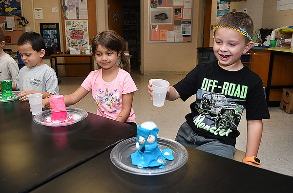 Brayden Havens, left, Macie Hicks and Carter Cook, made volcanoes then erupt them by pouring vinegar into baking soda during the STEM Camp held at Summers Co. High School. They were learning about underwater volcanoes.<br /> (Rick Barbero/The Register-Herald)