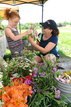 Willow Stover, 6, helps Sara Treadway, of Fayetteville build her own bouguet at Stover Heritage Farm's booth at New Roots Community Farm on 167 Wolf Creek Road in Fayetteville. The Farm host an open farm market every Thursday from 1-6 p.m.<br /> (Rick Barbero/The Register-Herald)