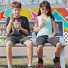 Siblings Karl, 11, and Emma, 8, take a rest from the rides on opening day of the State Fair of West Virginia in Fairlea Thursday. Jenny Harnish/The Register-Herald