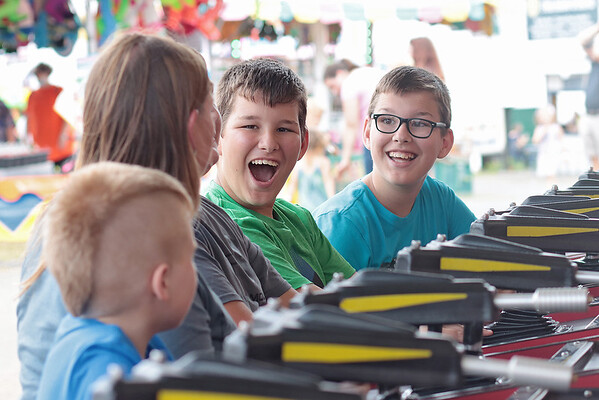 Twins Garrett Bowyer, 12, center, and Bryson Bowyer, 12, play the Water Race at the State Fair of West Virginia Wednesday. Jenny Harnish/The Register-Herald