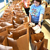 Denise Bragg, cook, left, and Donna Basham, head cook, Jumping Branch Elementary School bag up five days of breakfast and lunches for students because of COVID-19 remote learning.<br /> (Rick Barbero/The Register-Herald)