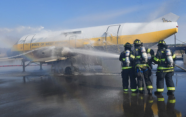 Members of Beaver Volunteer Fire Department hose down a simulator airplane during a mock disaster plane wreck held at the Raleigh County Memorial Airport in Beaver Tuesday morning. This is an training excerise that's conducted every three year for airport employees to be FAA certifield.<br /> (Rick Barbero/The Register-Herald)