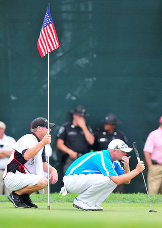 Troy Kelly and his caddy line up a putt on the 18th Green during the final round of The Greenbrier Classic on Sunday.Chris Tilley/The Register-Herald