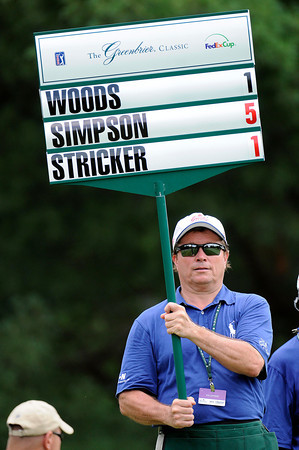 James Strawn, of Charleston, a Greenbrier Classic volunteer holds up the scores for Woods, Simpson and Stricker on the 8th hole.<br /> Rick Barbero/The Register-Herald