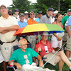 Ron Spellman, Roanoke, Va., left, and Grady Adams, Vinton, Va., shade themselves under a umbrella on the 8 th hole during the first round of The Greenbrier Classic held on The Old White TCP course in White Sulphur Springs.<br /> Rick Barbero/The Register-Herald