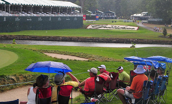 Even with storm warnings and rain  people still sit on the 18th hole during the second round of The Greenbrier Classic. Chris Tilley/The Register-Herald