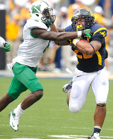 Shawne Alston, 20, of WVU, tries to break away from, Kieth Baxter, 8, of Marshall in the Friends of Coal Bowl game Saturday in Morgantown.<br /> Rick Barbero/The Register-Herald