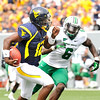 Geno Smith, 20, WVU, runs away from, Dominick LeGrande, 6, of Marshall for a touchdown in the Friends of Coal Bowl game Saturday in Morgantown.<br /> Rick Barbero/The Register-Herald