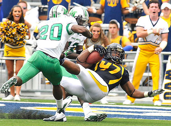 Doug Rigg, 47, WVU, gets tackled by, Steward Bulter, 20, and Rakeem Cato, of Marshall after intercepting a pass in the Friends of Coal Bowl game Saturday in Morgantown.<br /> Rick Barbero/The Register-Herald