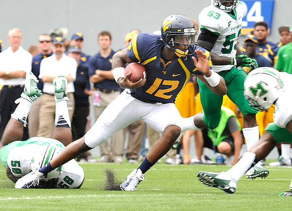 Geno Smith, of WVU, breaks away for some yardage against Marshall in the Friends of Coal Bowl game  Saturday in Morgantown.<br /> Rick Barbero/The Register-Herald