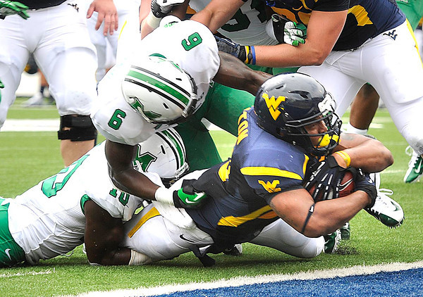 Shawne Austin, 20, of WVU, dives across the goal line for touchdown against Marshall in the Friends of Coal Bowl game Saturday in Morgantown.<br /> Rick Barbero/The Register-Herald
