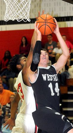 """F. BRIAN FERGUSON/THE REGISTER-HERALD=Oak Hill""""s DeMarcus Hughes, left, defends as as Westside's Corey Bowles, right, drives for the basket during Friday evening action in Oak Hill."""