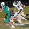 Aaron Krise, 8, of Fayetteville left, tries to break away from, Tyler Parker, 32, and Dylan Duncan, 52, of Greenbrier West, during game Friday night in Fayetteville.<br /> Rick Barbero/The Register-Herald