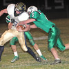Hunter Pullens, 6, of Fayetteville, right, tries to pull down, Tyler Parker, 32, of Greenbrier West, during game Friday night in Fayetteville.<br /> Rick Barbero/The Register-Herald