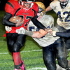 F. BRIAN FERGUSON/THE REGISTER-HERALD=Oak Hill's ,Jalen Jones, left. picks up yards against Shady Spring's , Tyler Harper, center, and Robby Perry, right. during the Red Devils Homecoming game in Oak Hill.