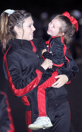 F. BRIAN FERGUSON/THE REGISTER-HERALD=Oak Hill cheerleader Hanna Powers, left, and Midget League cheerleader Sharon Smith, right, share a moment during the Homecoming game in Oak Hill.