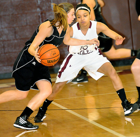 F. BRIAN FERGUSON/THE REGISTER-HERALD= Winfield's #4 drives the ball as Woodrow Wilson's LaShonda McDowell defends during Wednesday evening action in Beckley.