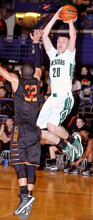 Wyoming East Cody Lester takes a jump shoot over Summers County T.J Smith during Tuesday nights sectional game at the Beckley Convention center. Photo by Chris Tilley
