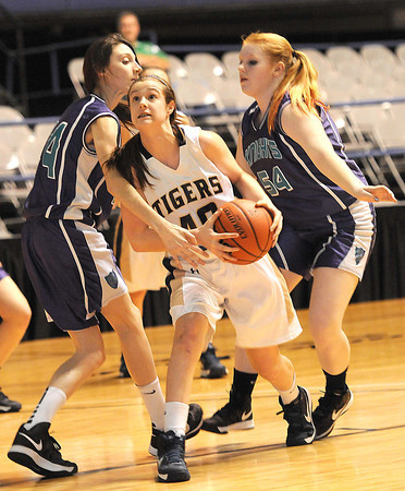 Abigail Gwinn, 40, of Shady Spring Middle School, drives to the basket between Lauren Lindsey, 24, left, and Kerri Arbuckle, 54, of Eastern Greenbrier Middle School, during the Big Atlantic Classic championship game at the Beckley-Raleigh County Convention Center.<br /> Rick Barbero/The Register-Herald