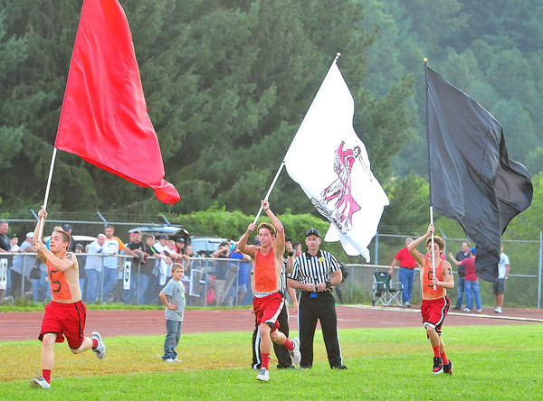 From right to left Michael Prater, Austin Lyons, and Chris Kincaid run the Liberty High School Football field waving flag with the the school colors.