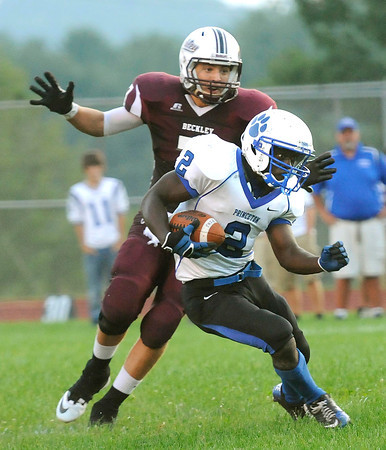Tahj Sho-Johnson, 2, of Princeton, breaks away from a Woodrow Wilson defender at Van Meter Stadium in Beckley Friday, August 24, 2012.<br /> Rick Barbero/The Register-Herald