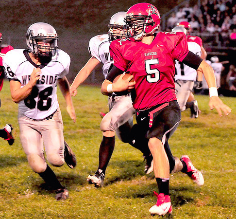 Liberty High School Joey Lacek runs the ball with Westside's Jeffrey Brown trying to make the tackle.