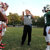 F. BRIAN FERGUSON/THE REGISTER-HERALD=Head Referee Edward Miller flips the coin to kick off his 44th year wearing the stripes as Fayetteville's Aaron Krise, right, looks on and Wahama square off in Fayetteville. Aug. 24, 2012.