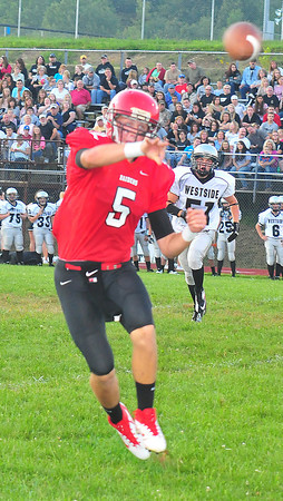 Liberty High School Joey Lacek, looks for the open man in their home game with Westside High School Friday Night.