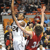 Donte Nabors, left, of Woodrow Wilson,  drives to the basket against, Ian Miles, of Hurricane, during the boys state quarter final game at the Charleston Civic Center Wednesday morning.<br /> Rick Barbero/The Register-Herald