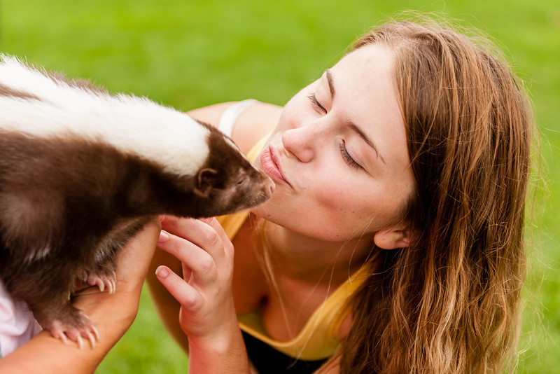 Girl kissing a skunk.