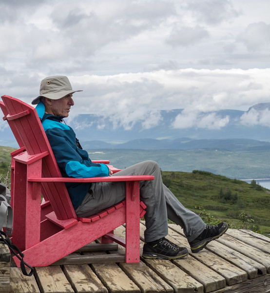 "One of the best things about visiting Newfoundland is the spectacular hiking. <br /> <br /> Parks Canada, as part of their Canada 150th celebration branding, placed these red Adirondack chairs throughout the country's parks. <br /> <br /> Given the steep trail we climbed to get to this vantage point, we suspect that a helicopter played a part in positioning this one.<br /> <br /> It has been suggested that this shot should be titled ""John's nose visits Bonne Bay"". Some people are cruel, I say."