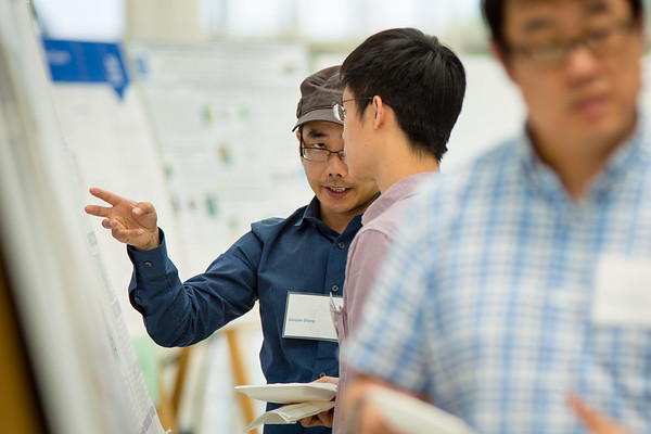 Guojian Zhang (left) speaks about his poster Xiaozhuo Liu (right) at the start of the the 9th Annual Postdoctoral Research Symposium hosted by the Office of Postdoctoral Scholars on June 9, 2017 at the UB Center for the Arts on north campus. <br /> <br /> Photographer: Meredith Forrest Kulwicki