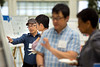 Guojian Zhang (left) speaks about his poster Xiaozhuo Liu (right) at the start of the the 9th Annual Postdoctoral Research Symposium hosted by the Office of Postdoctoral Scholars on June 9, 2017 at the UB Center for the Arts on north campus. In the foreground, Ken Wakabayashi (blue plaid) speaks with R. Lorraine Collins, co-director for the postdoctoral training program.<br /> <br /> Photographer: Meredith Forrest Kulwicki