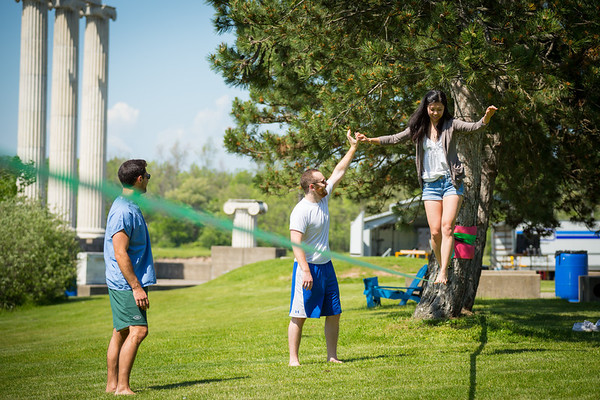 Shelby Lee gets a hand from Ian Lieberman practicing slacklining while Mike Healy watchs near Baird Point on north campus. All three are dental students.<br /> <br /> Photographer: Meredith Forrest Kulwicki