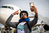 The UB Bulls Football team boards the plane heading to the Makers Wanted Bahamas Bowl on Dec. 16, 2019. Marlyn Johnson poses for a photo by the plane.<br /> <br /> Photographer: Meredith Forrest Kulwicki